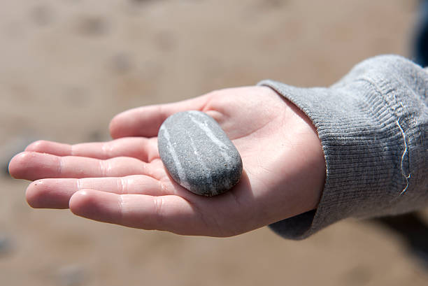 Close Up Image Of Young Boys Hand Holding Pebbles From A Beach