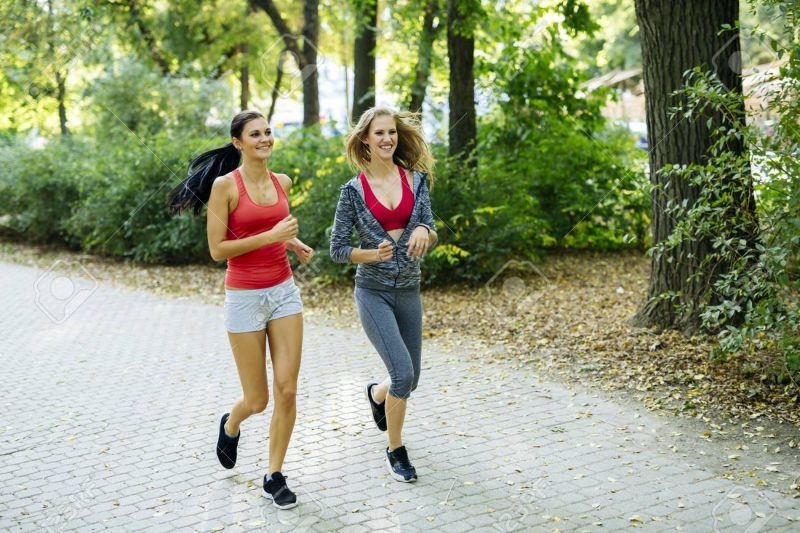 50754580 Two Young Women Jogging In Nature In Pursuit Of A Perfect Body Figure