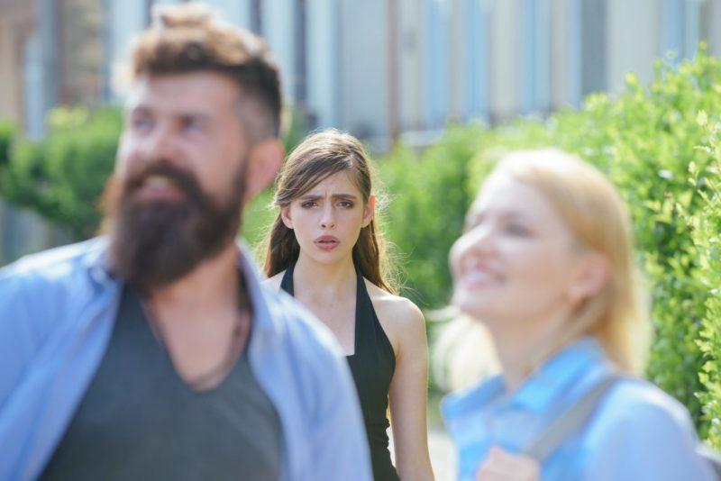 Woman Unhappy Behind Man